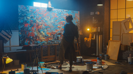 Fototapete - Talented Female Artist Works on Abstract Oil Painting, with Broad Strokes of Paint Brush She Creates Modern Masterpiece. Dark and Messy Creative Studio where Large Canvas Stands on Easel Illuminated