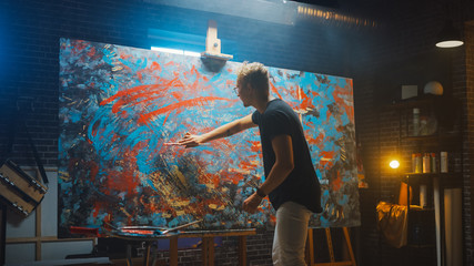 Fototapete - Talented Male Artist Energetically and Violently Using Paint Brush She Creates Modern Masterpiece of the Oil Painting. Dark and Messy Creative Studio with Large Canvas of Striking Colors