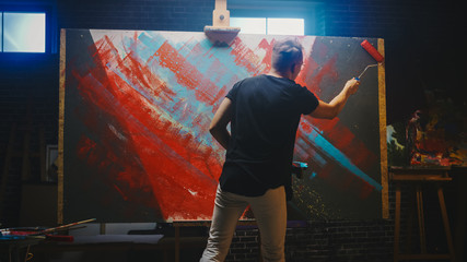 Fototapete - Talented Male Artist Working on a Abstract Painting, Uses Industrial Roller To Create Daringly Emotional Modern Picture. Dark Creative Studio Large Canvas Stands on Easel Illuminated
