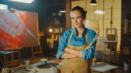 Fototapete - Professional Young Female Artist Dirty with Paint, Wearing Apron, Arms Crossed while Holding Brushes, Looks at the Camera with a Smile. Authentic Creative Studio with Large Canvas.
