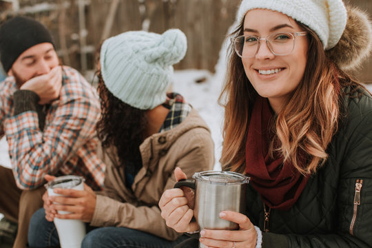 Group of Friends Sitting with Coffee at Winter Campsite