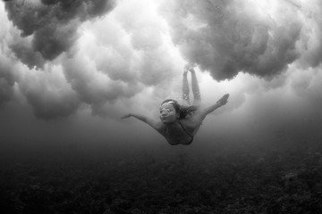 Black and white image of a female freediving. Underwater dance. Conceptual, art