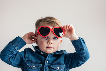 portrait of a toddler wearing heart sunglasses