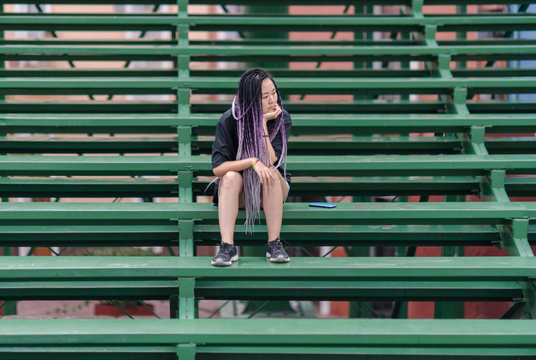 Young cool woman alone on a stadium bench
