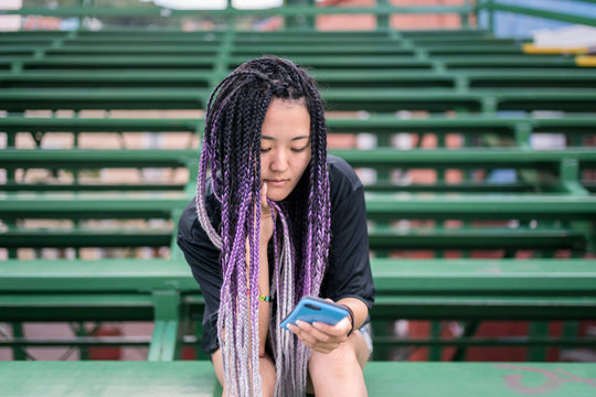 Young woman with rasta braids with her phone