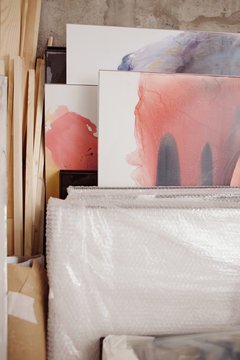 Stacked paintings with abstractions in studio