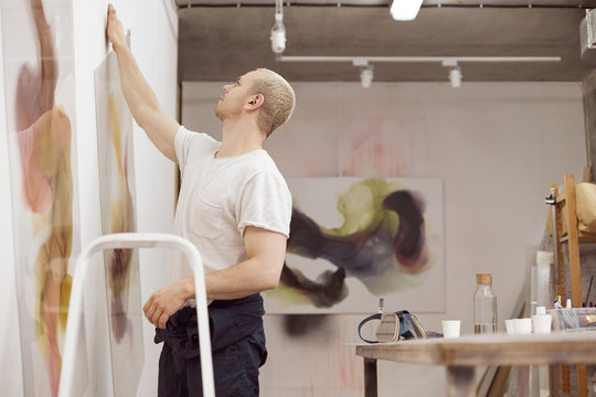 Man in art studio with painting on wall