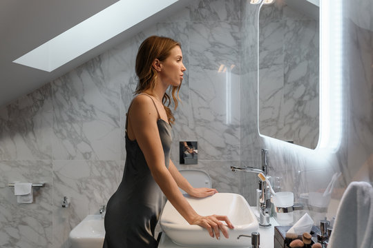 Attractive woman looking in mirror in bathroom