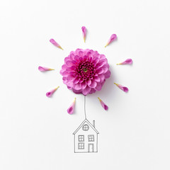 Bright pink natural flower with drawing of a house on a gray bac