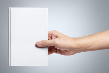 Hand holding a blank white hard cover book on gray background