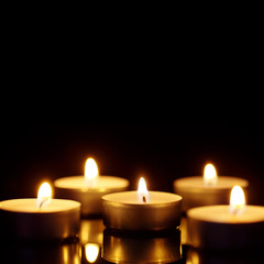 Burning candles with copy space on black background, shot with shallow depth of field