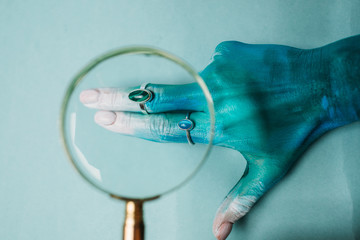 Painted hand in rings through magnifying glass