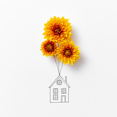 Creative drawing of a house with natural orange flowers on a gra