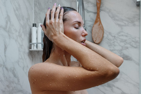 Young woman showering sensually at home