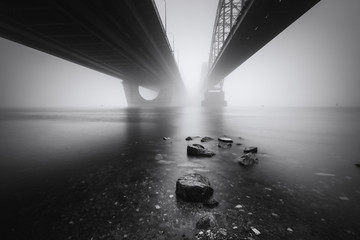 View under the big bridges across foggy Dnipro river in Kyiv. Ukraine.  Architecture in timeless...