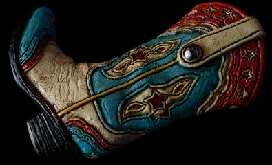Sculpted red white and blue cowboy boot on side isolated on black background