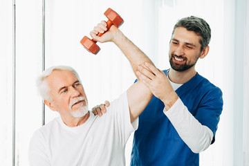 Positive physiotherapist helping his senior patient to lift a dumbbell. Physio treatment at rehab center