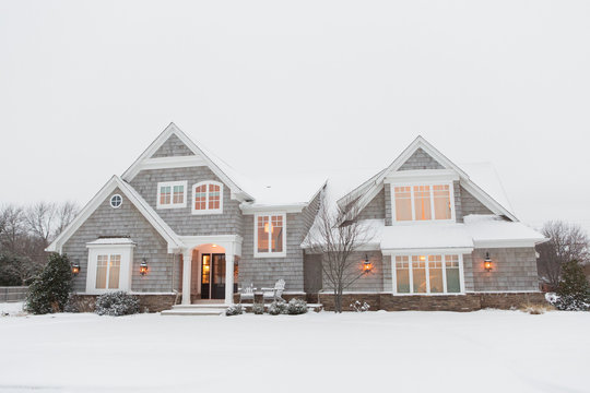 Wood shingled home in snow with warm lights illuminating windows
