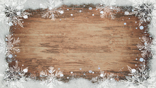 winter / Advent / christmas Background template - Frame made of snow with snowflakes and ice crystals on brown wooden texture, top view with space for text