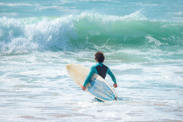 Surfer with surfboard at the beach