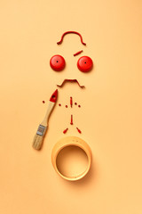 Geometric creative pattern from alarm clock's parts in the form of man's upset face with painting brush isolated on a pastel background.
