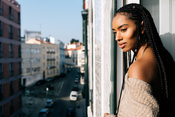 Beautiful black woman with braided long hair standing in a balcony