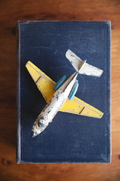 Concept for travel, vintage airplane sits atop an old book