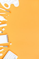 Assorted office and school white stationery on  trendy saffron orange background monochromatic with copy space