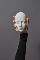 Girl's hand in a black jumper holds gypsum face sculpture on a gray background. Concept social psychological masks