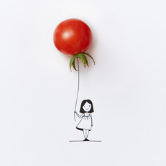 Girl's graphic sketch with balloon in the shape of red tomato on a white background with copy space.
