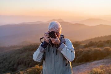 Senior traveler taking photos of countryside