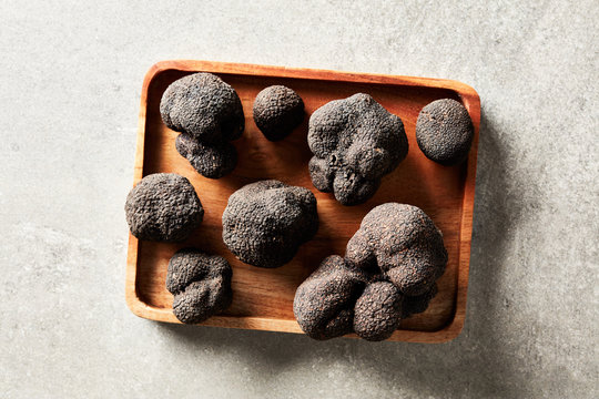 Delicious black truffles on wood tray