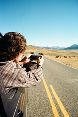 young man takes picture out car window