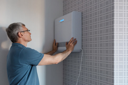 Man installing modern air conditioner