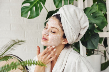 Obraz Young woman applying face mask at home. Natural Skin Care Routine. Cleaning face with natural cosmetics. - fototapety do salonu