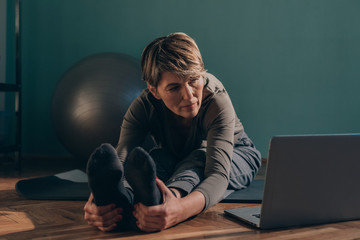 Woman doing yoga while watching laptop at home