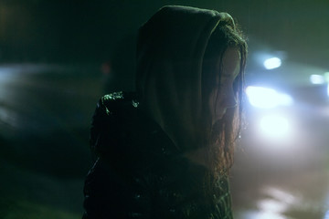 portrait of a girl in the rain in wet clothes on the background of the road by the headlights of the car
