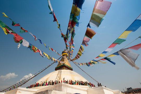 Prayer flags at Buddha Stupa against cloudy sky, Nepal