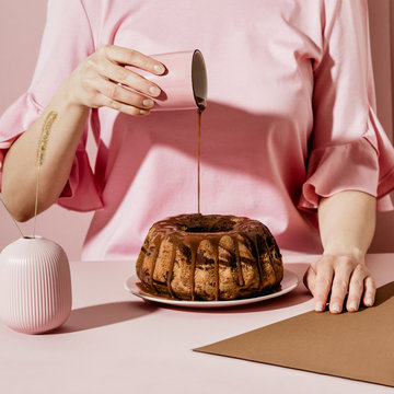 Midsection of woman pouring sugar syrup on bundt cake