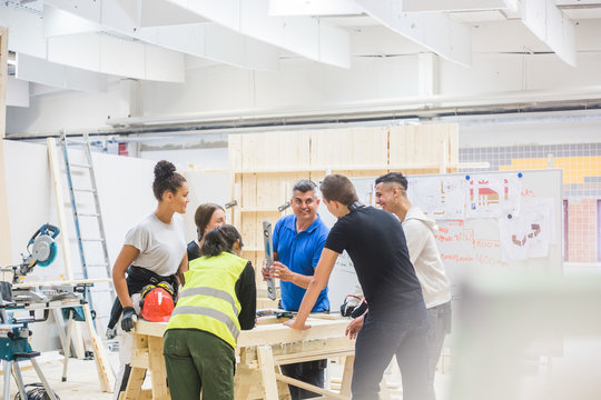 Male instructor teaching about level to trainees standing at workbench in illuminated workshop