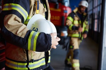 Midsection of female firefighter with protective helmet standing at fire station
