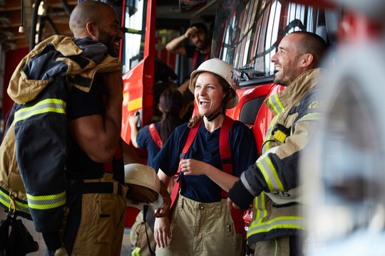 Happy firefighters talking while standing against fire engine at fire station