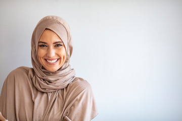 """Modern, Stylish and Happy Muslim Woman Wearing a Headscarf. Arab saudi emirates woman covered with beige scarf. """"Welcome"""" Face. One women smile with white background"""