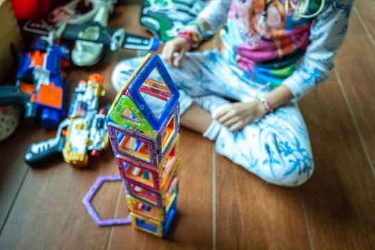 Little girl playing to build a tower with magnetic pieces of plastic colors.