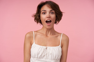 Surprised pretty young brunette woman with short haircut looking at camera with wide eyes and mouth opened, posing over pink background with hands down
