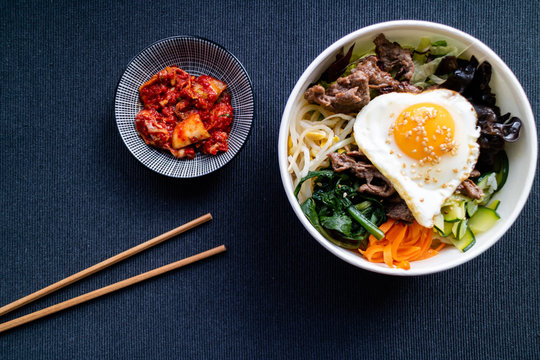 Bi bim bap with beef and kimchi on dark background. Korean cuisine. Top view.