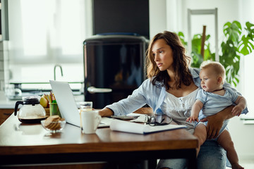 Young mother working on laptop while being with baby at home.