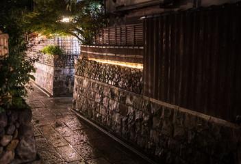 Narrow stone street through traditional Japanese neighborhood