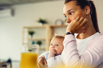 Young mother feeling worried and thinking of something at home.