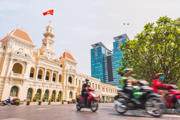 Ho Chi Minh City, Vietnam: Saigon City Hall, Vincom Center towers and colorful street traffic blurred in motion. Saigon downtown with its famous landmarks. Stock image with removed logos.